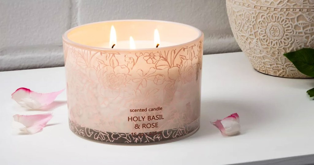 lit 3 wick candle on a white table with flower petals near it
