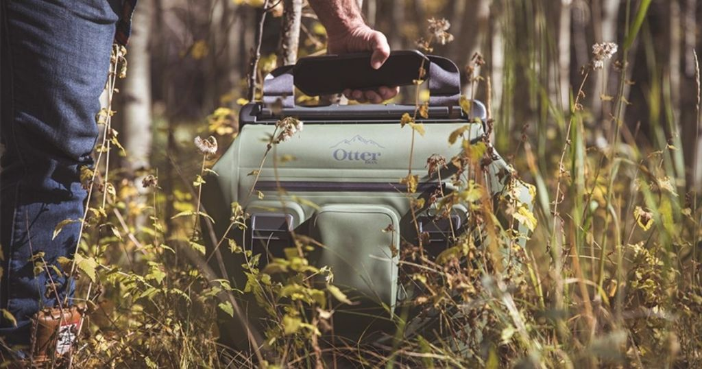 green Otterbox cooler in woods