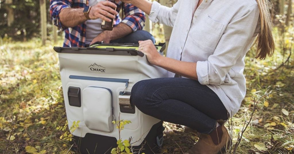 woman kneeling next to a otterbox cooler