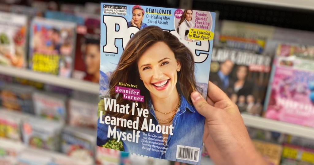 hand holding people magazine