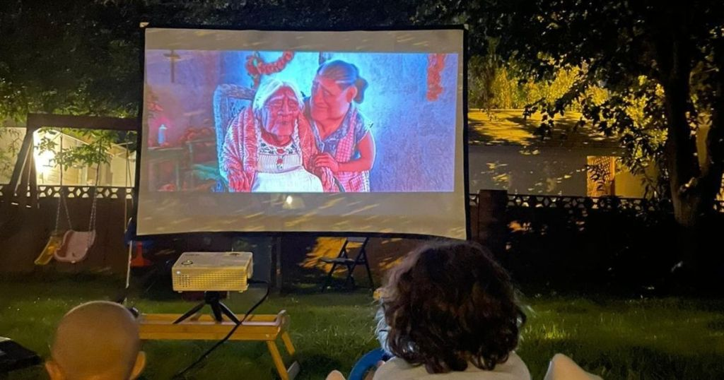people watching move on projector in backyard