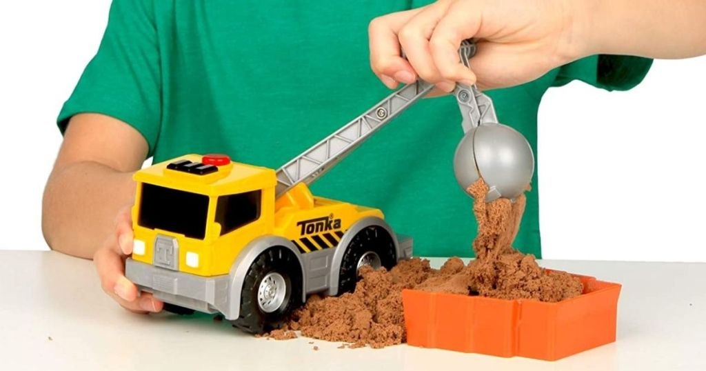 little boy playing with a Tonka trunk