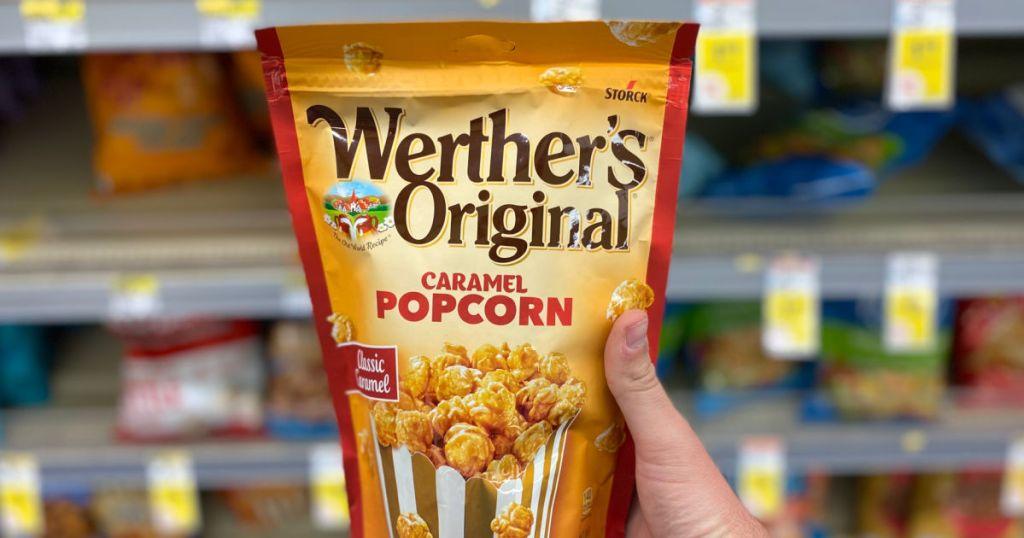 hand holding bag of caramel popcorn