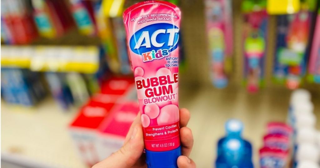 hand holding pink tube of toothpaste
