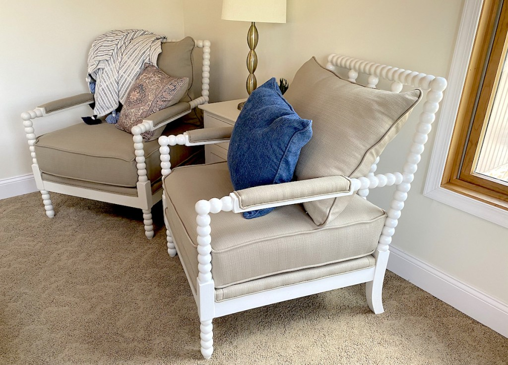 two white beaded chairs with tan cushions and throw pillows sitting on carpet floor