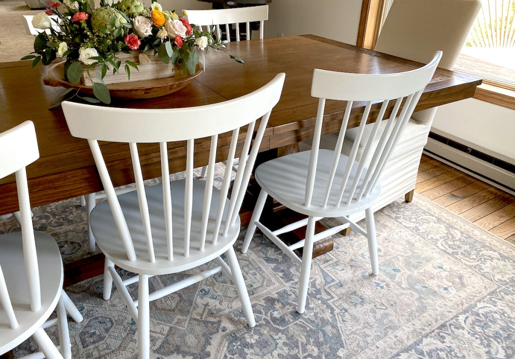 close up of dining room table and white chairs