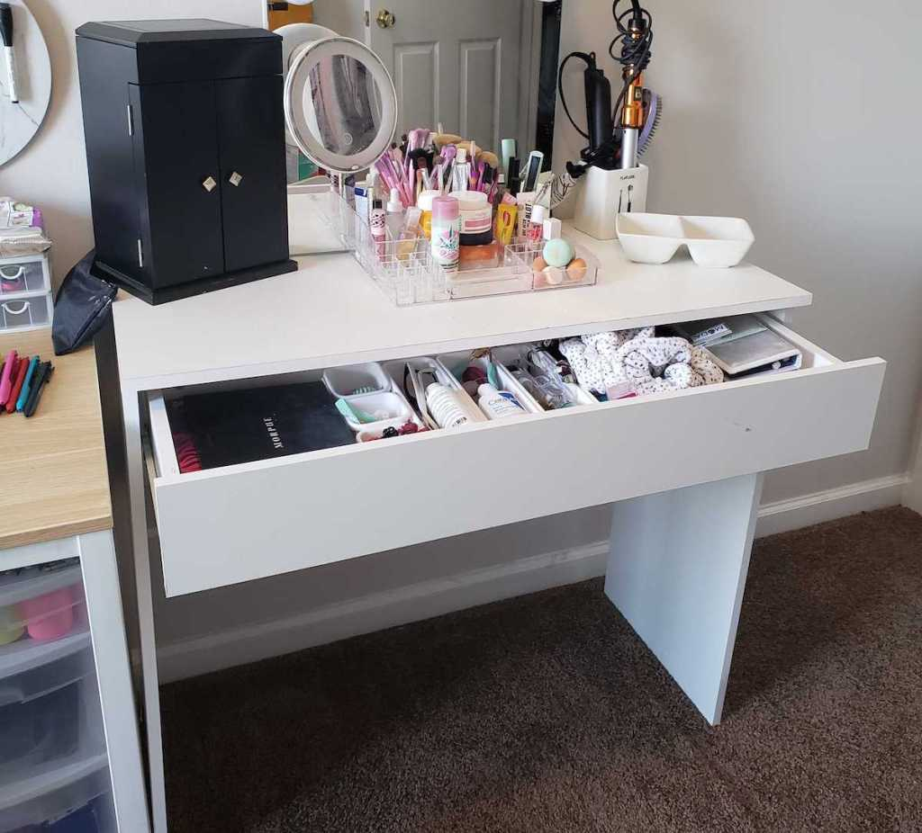 white vanity desk with drawer open and full of cosmetics