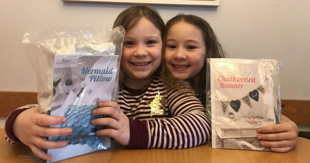 two girls holding craft kits