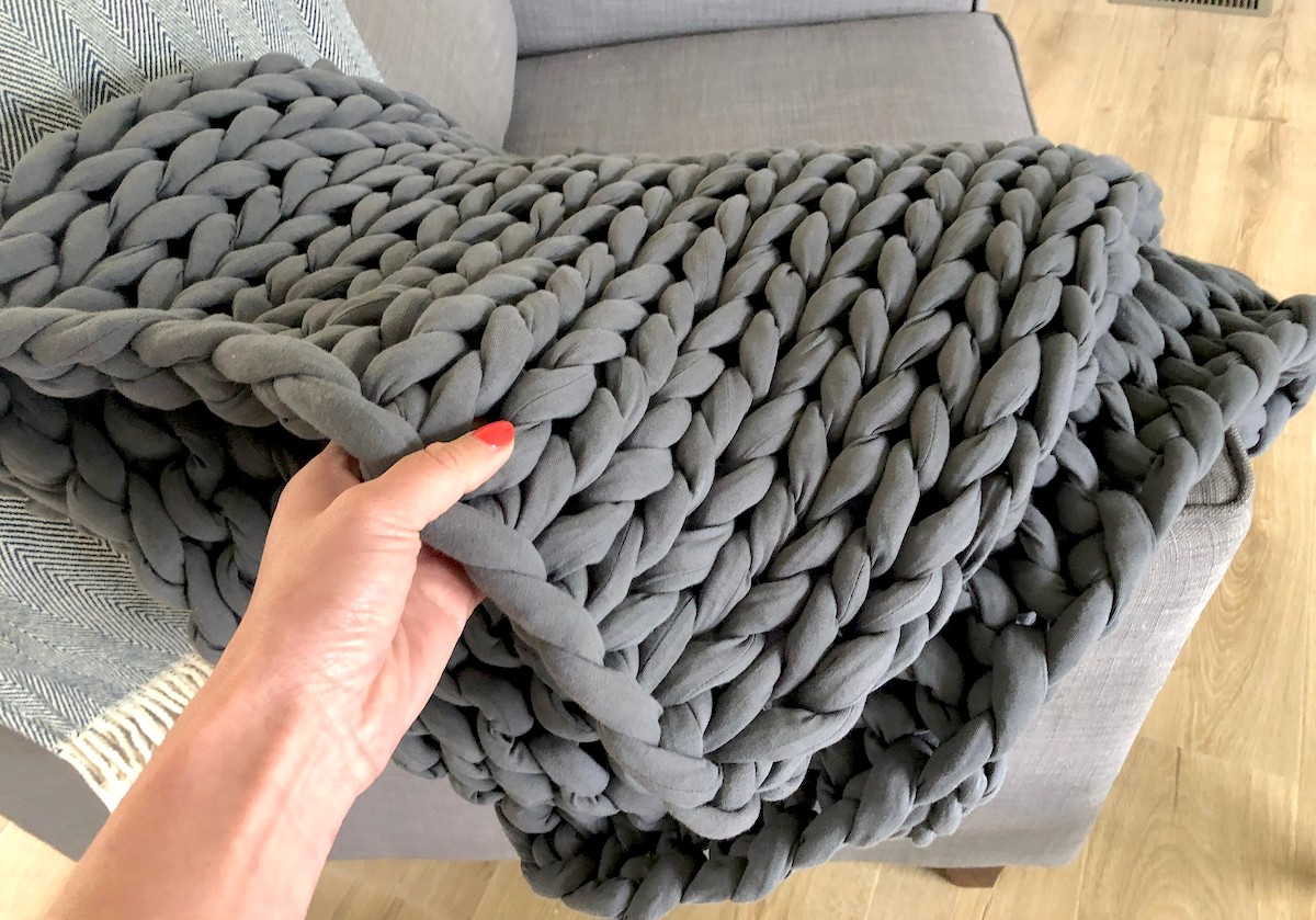 hand holding corner of gray bearaby weighted blanket