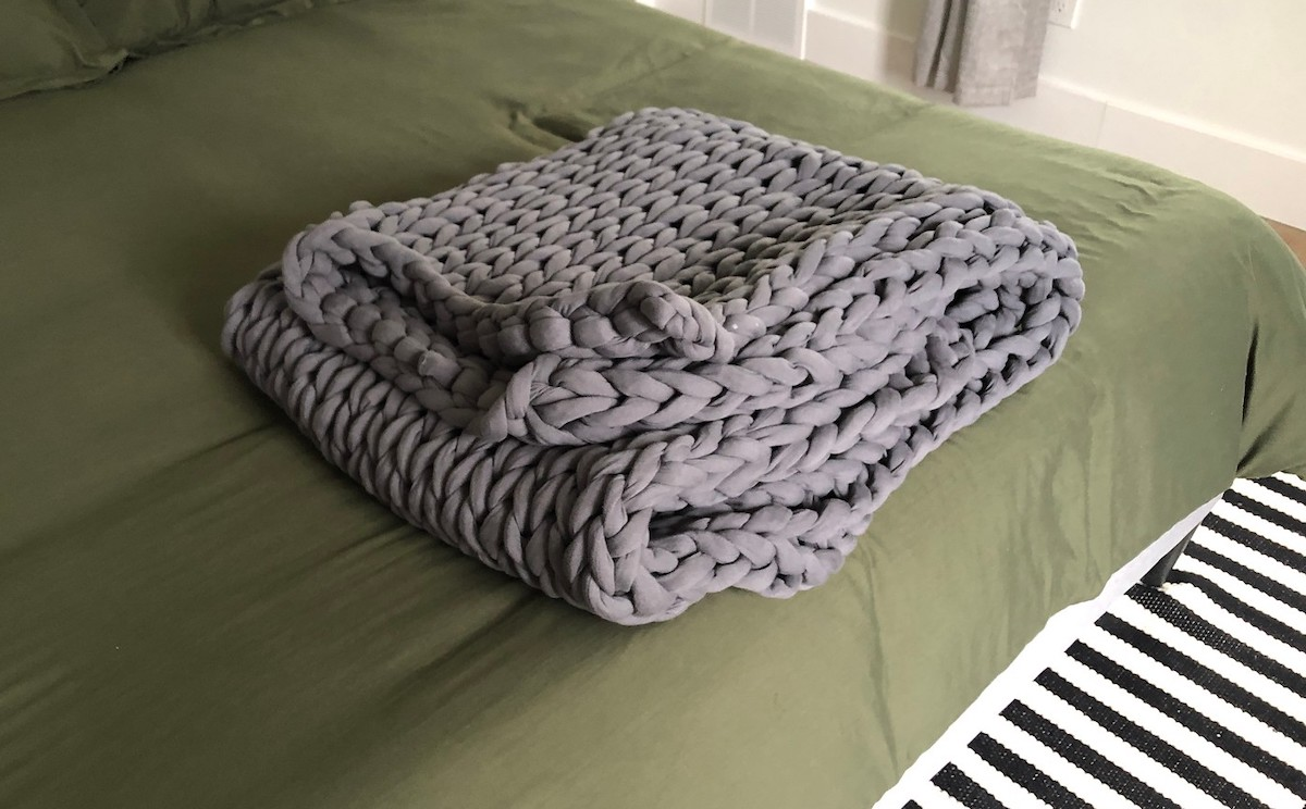 folded gray weighted chunky knit blanket on edge of green bed