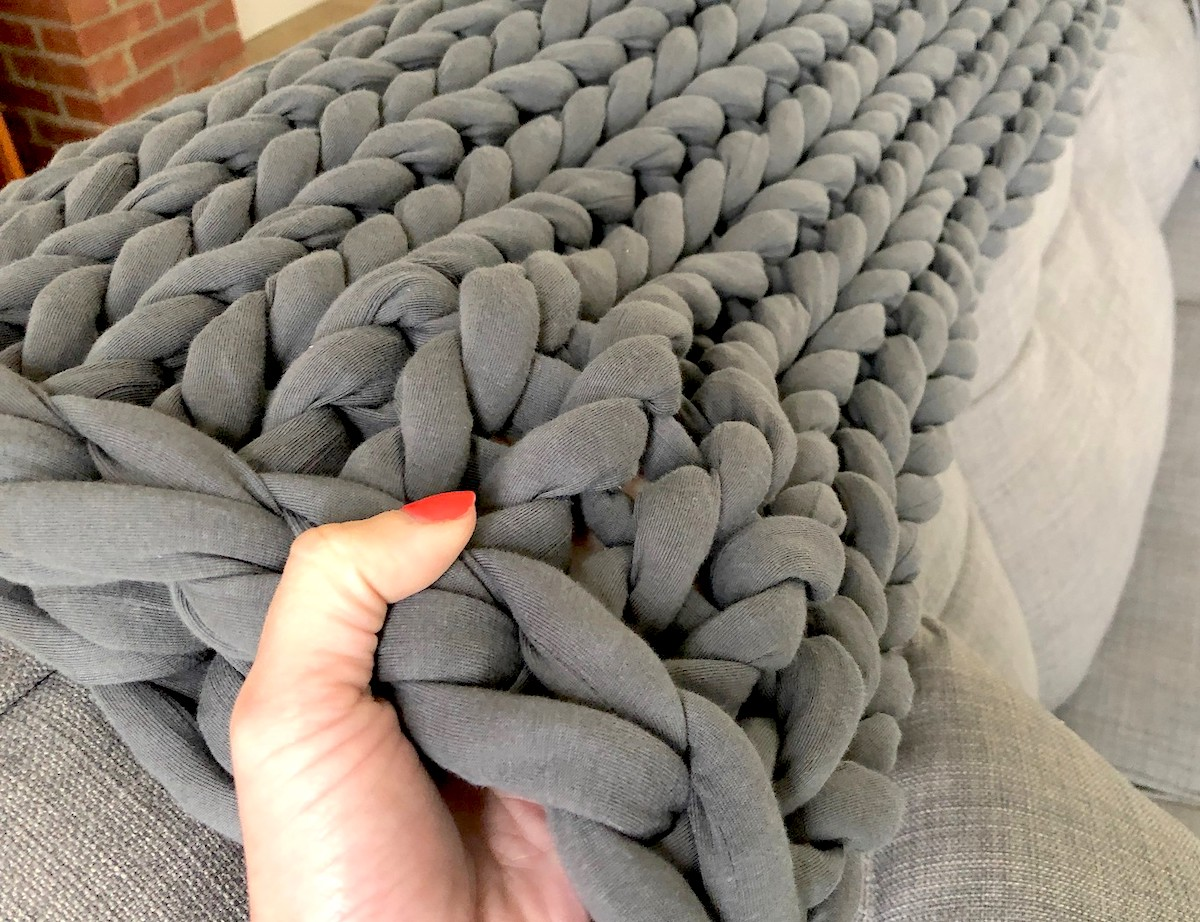 hand holding edge of chunky knit throw blanket on couch