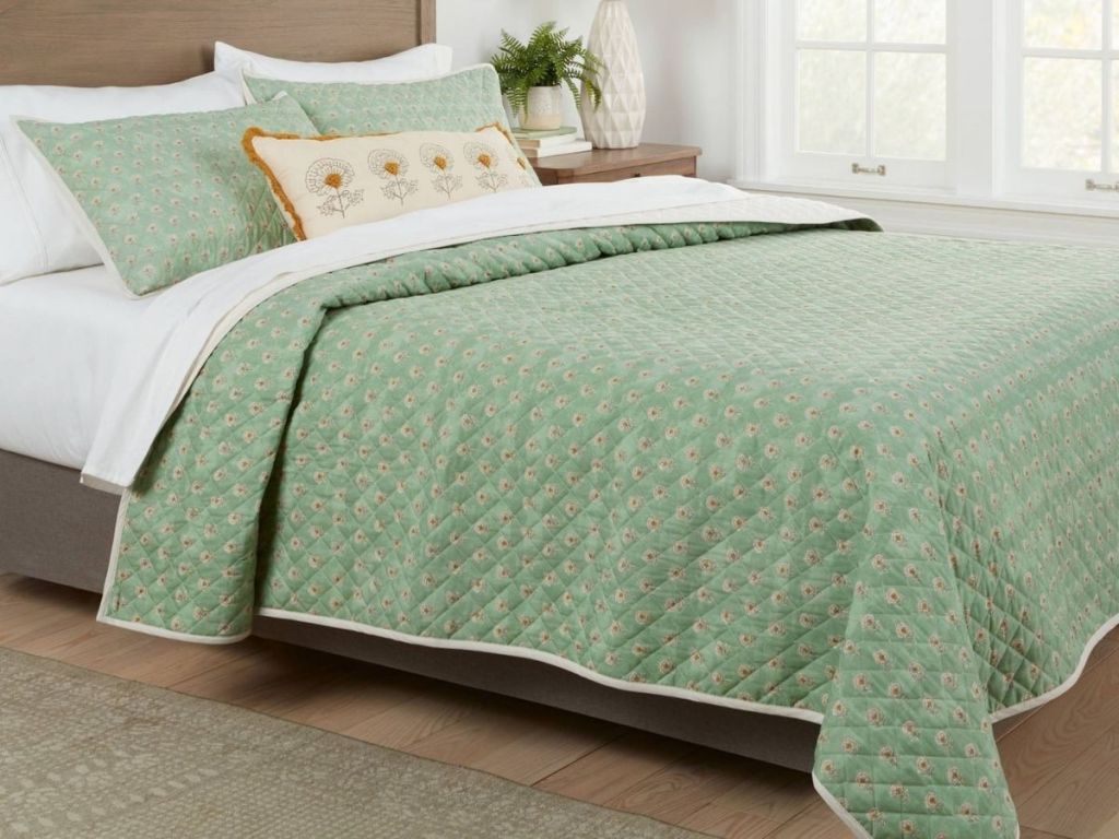 Green quilt bedding on bed