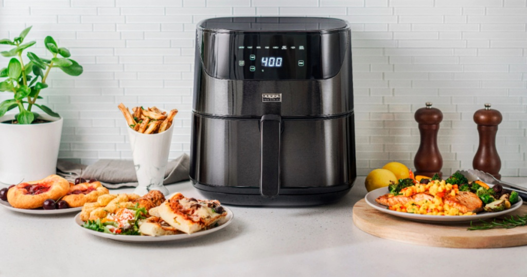 black air fryer surrounded by food on a counter