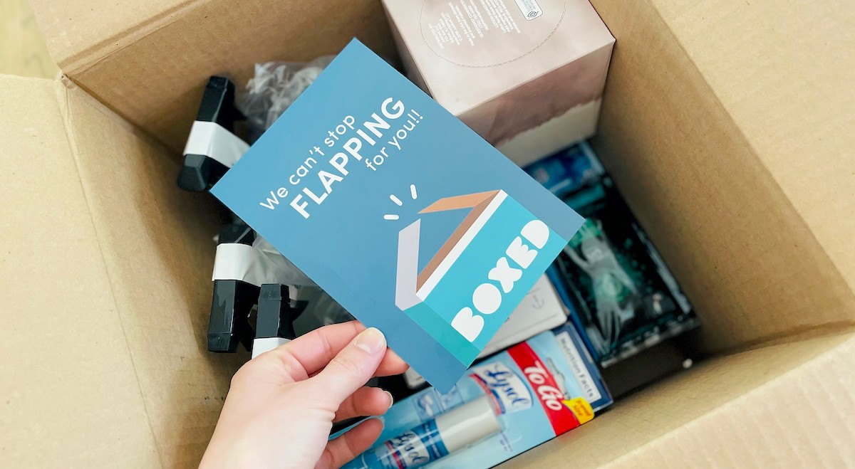 hand holding card over box full of groceries from Boxed promo code