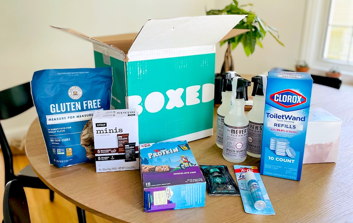 spread of household essentials and food on dining room table from boxed with promo code