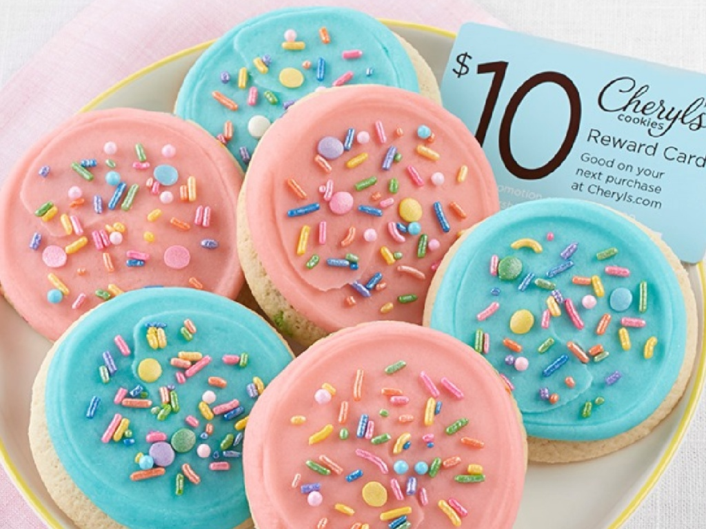 plate with six cookies that have blue and pink frosting and a gift card