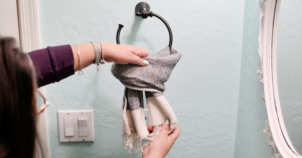 demostrating how to hang a hand towel