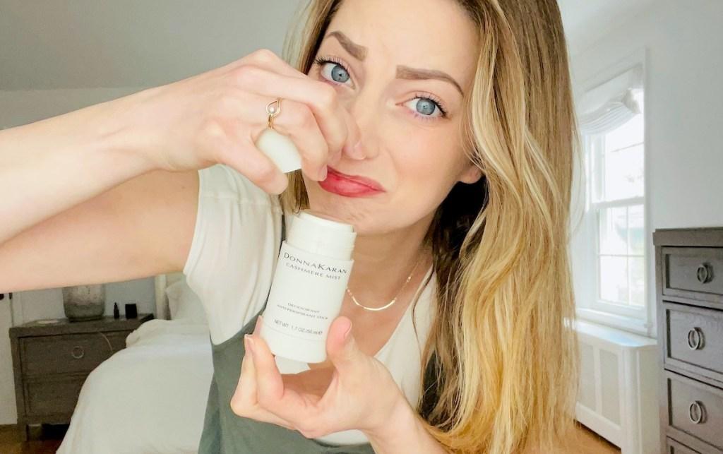 woman plugging nose holding donna karan cashmere mist deodorant