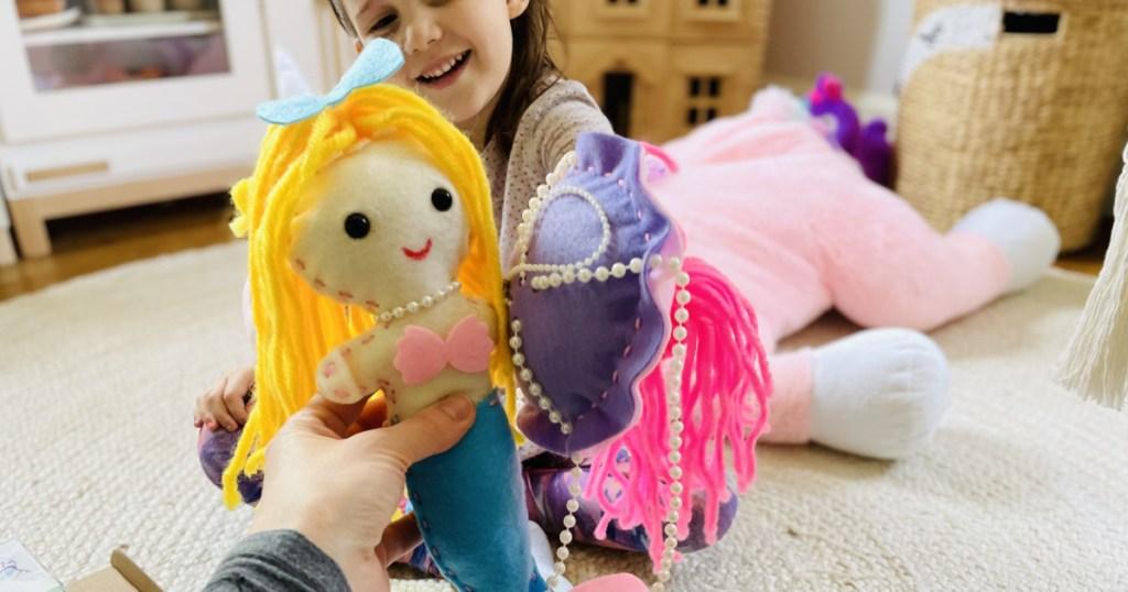 holding kids sewing kit