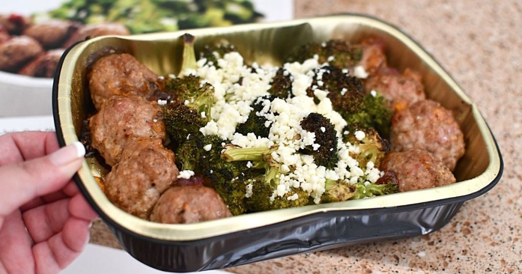 hand holding tray of meatballs and brocolli