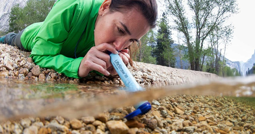woman usiong lifestraw in water