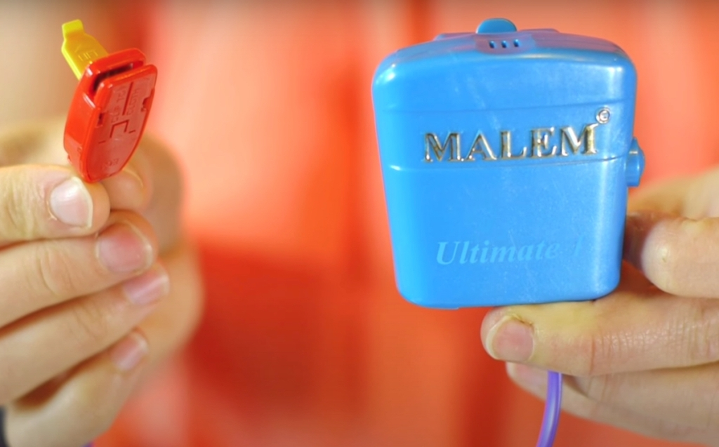 person holding malem bed wetting alarm in hand