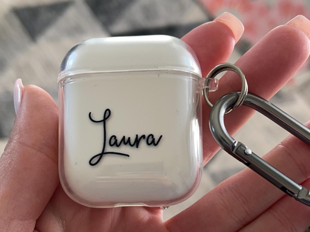 woman holding a personalized AirPods case with the name Laura
