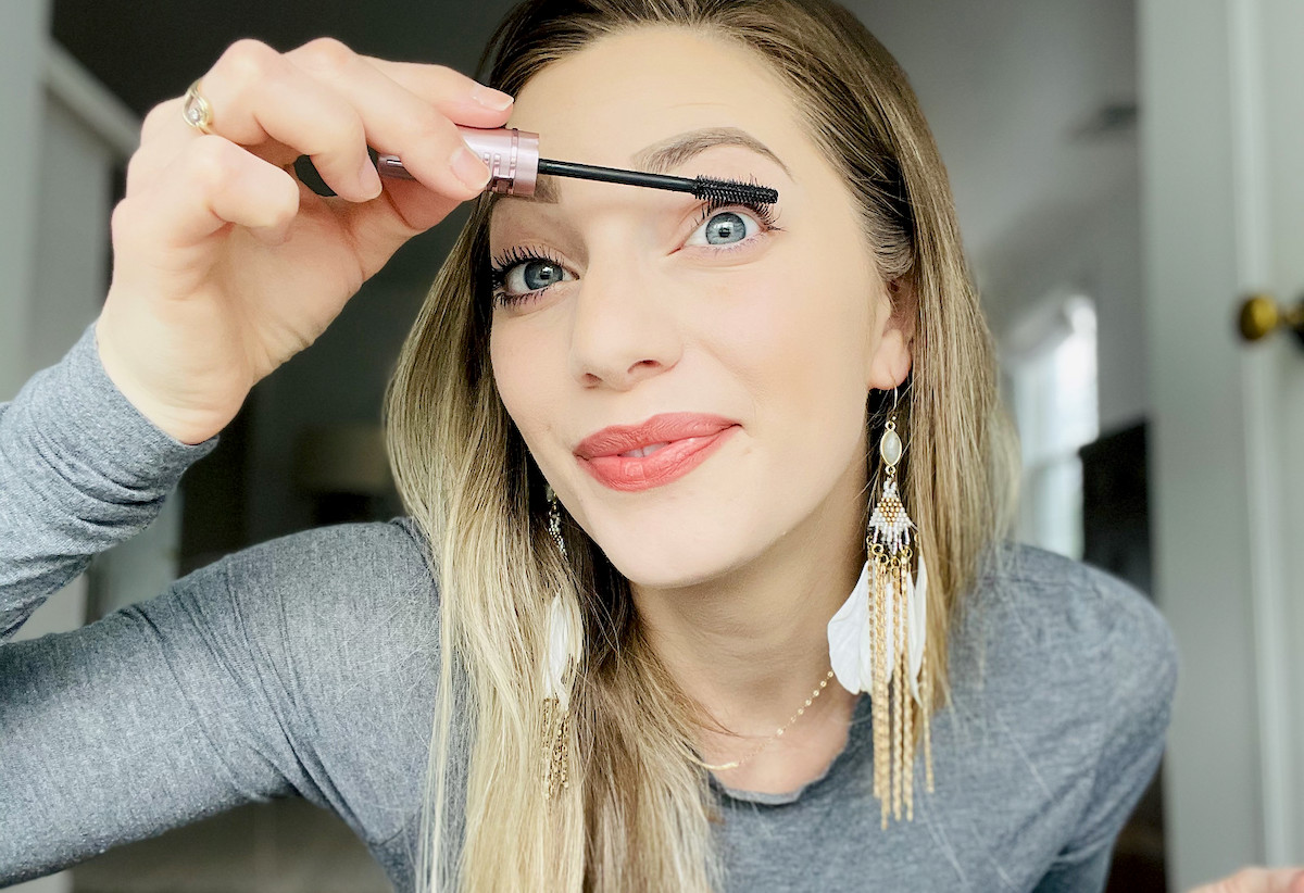 woman putting on maybelline sky high mascara