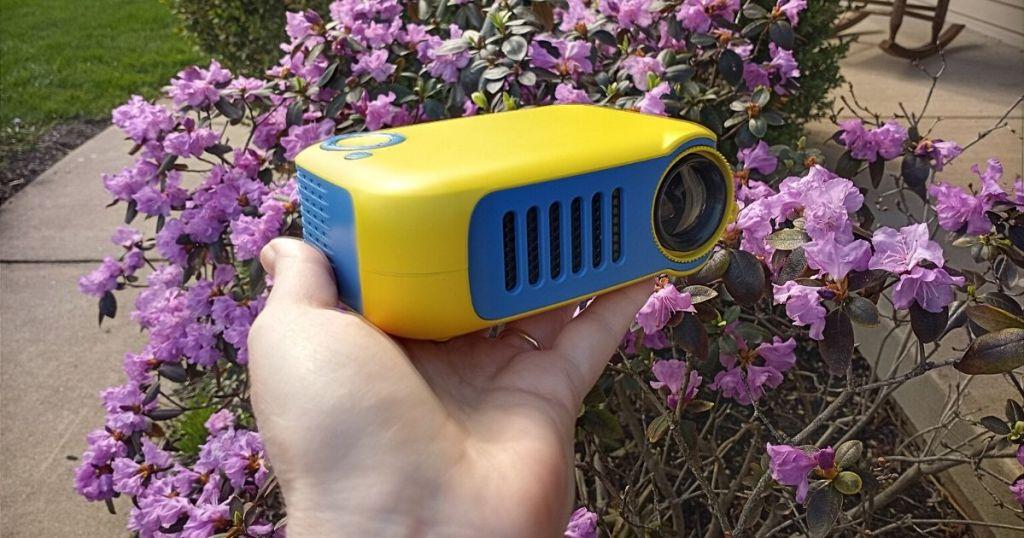 itari mini projector (1) in hand near flowers