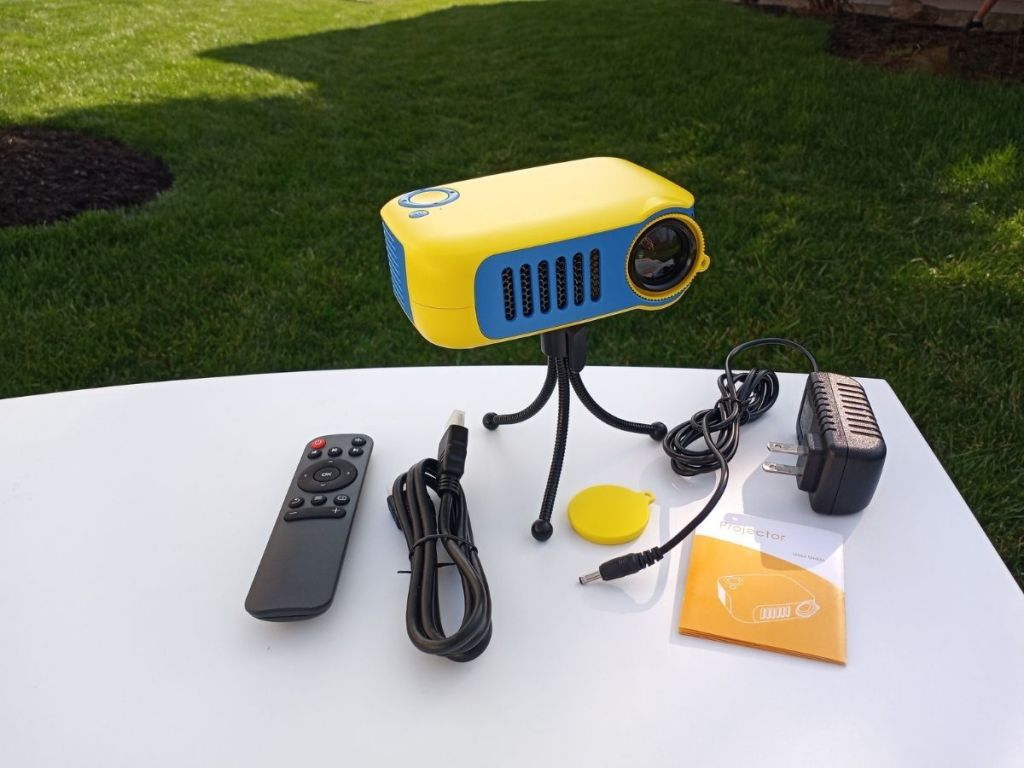 yellow and blue mini projector on tripod with accessories on table