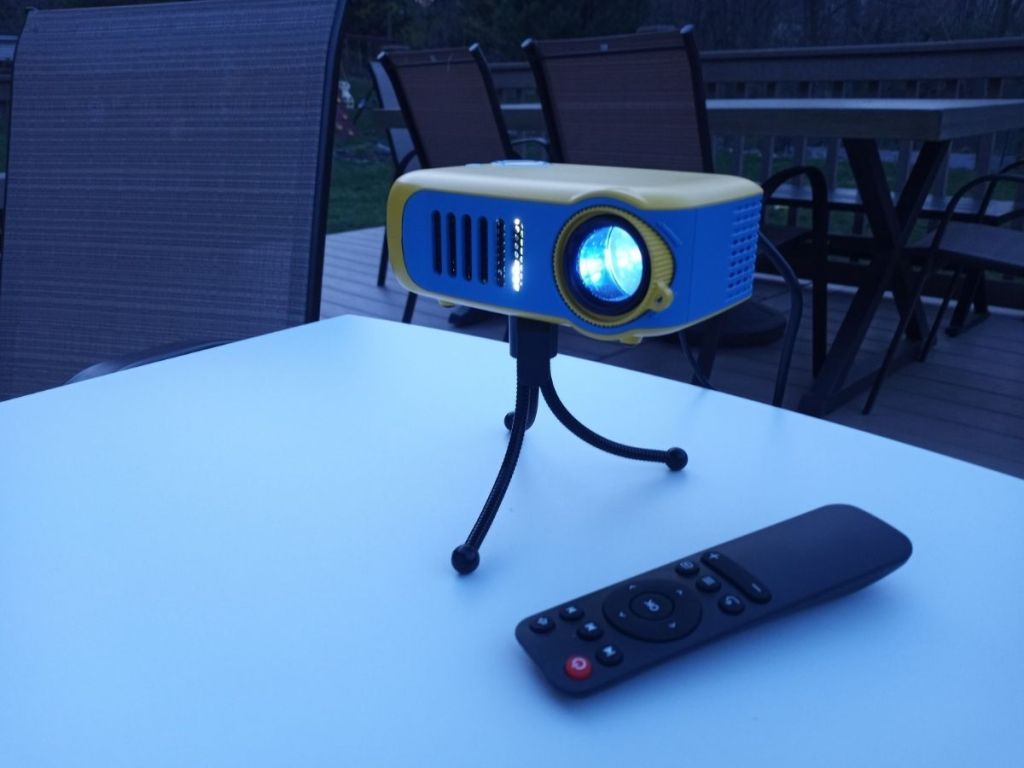 mini projector on tripod on table by remote