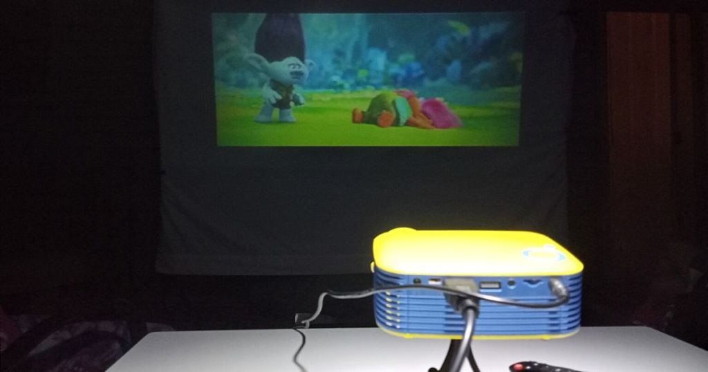 mini yellow and blue projector projecting Trolls movie