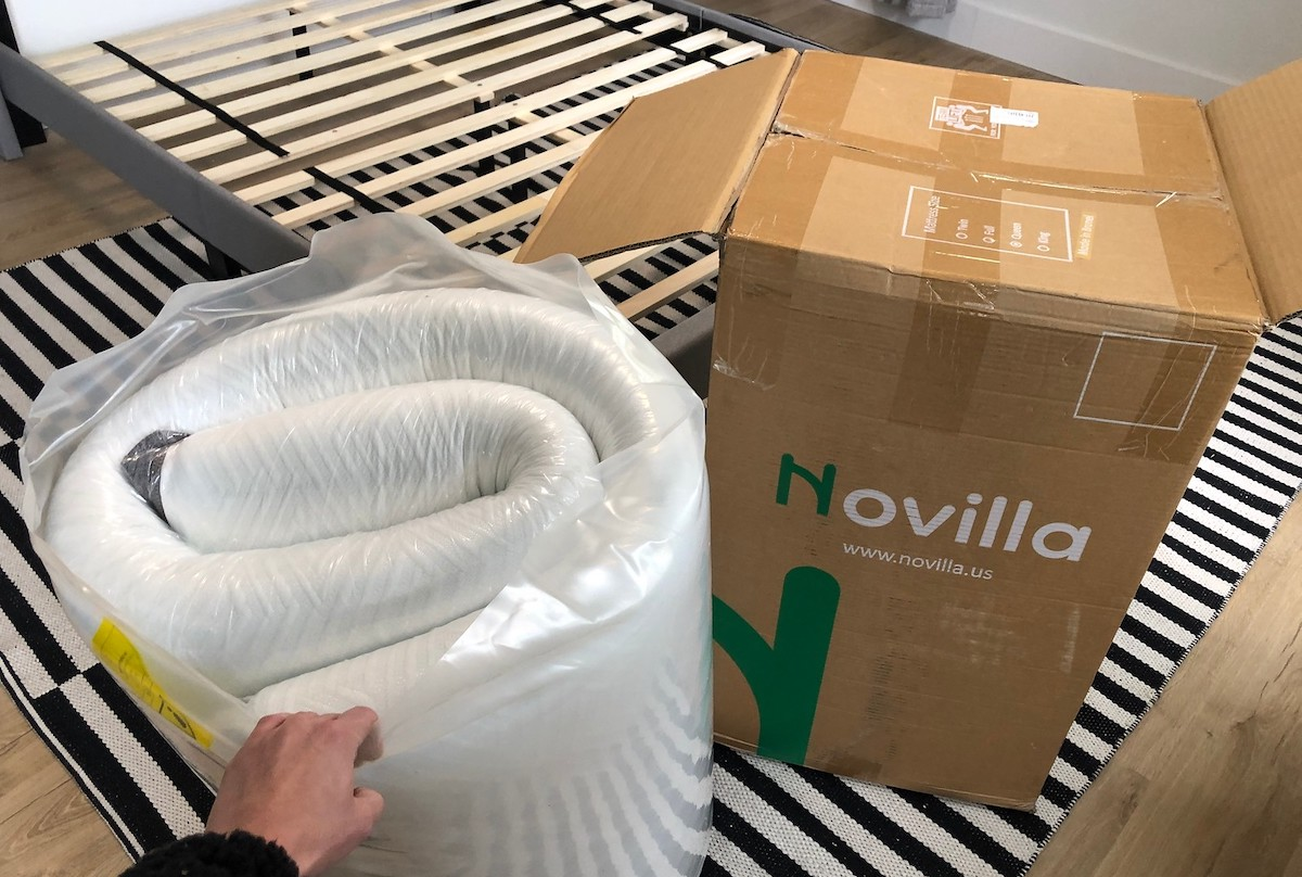 hand holding rolled up mattress in bag