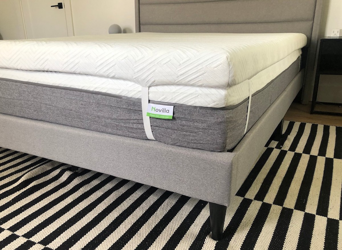 close up of mattress on gray upholstered bedframe