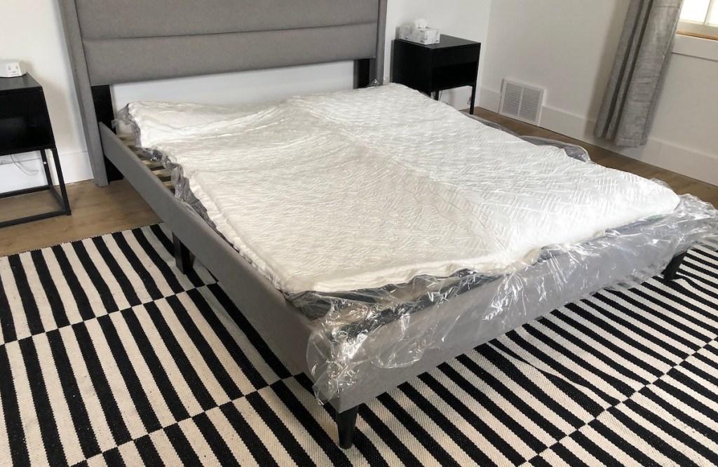 unrolled mattress on bedframe