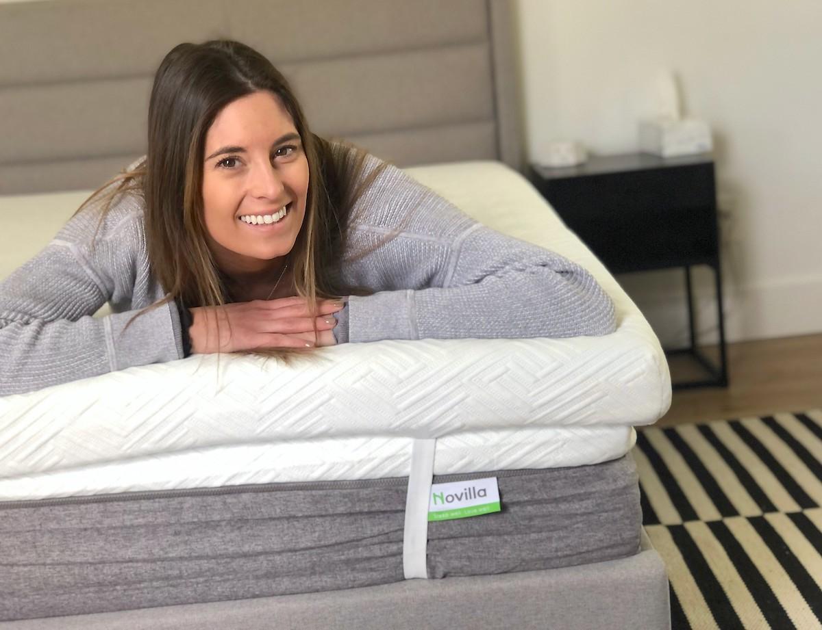 woman smiling at camera laying on bare mattress