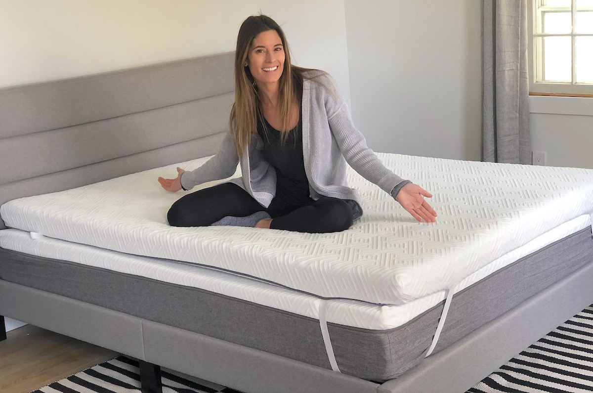 woman sitting on novilla mattress with hands out to the side