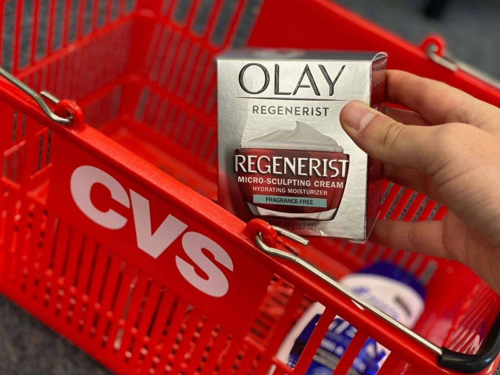 hand holding a box of Olay Regenerist by a CVS basket