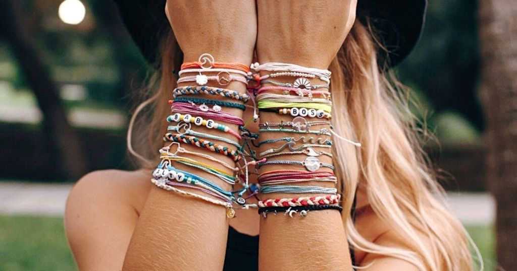 woman holding wrists up covered in bracelets