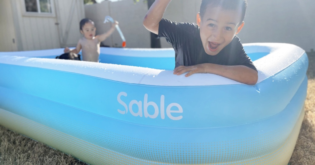little boy in sable family sized inflatable pool