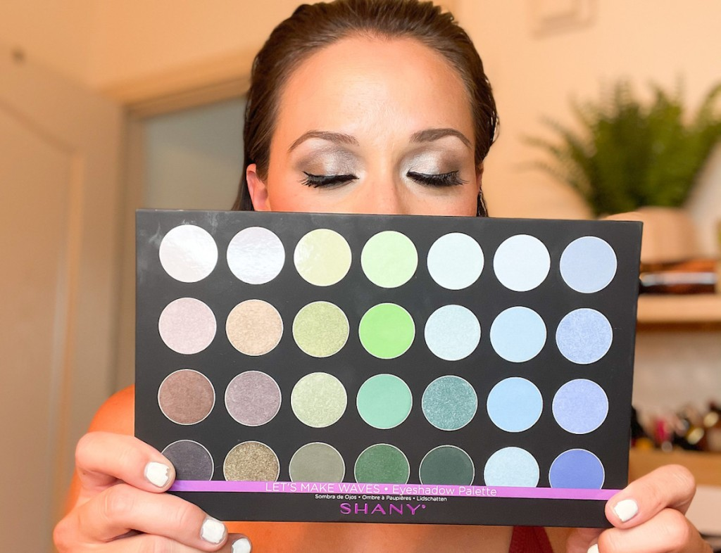 woman holding up shany cosmetics makeup palette with glam eyeshadow on face