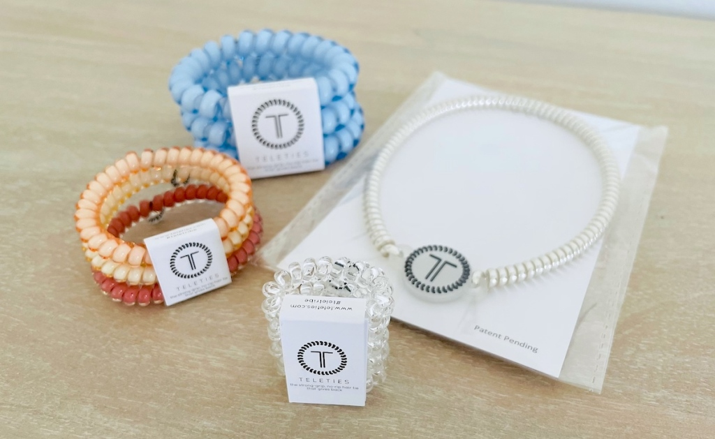 various styles and colors of teleties hair ties and headband in packaging on table