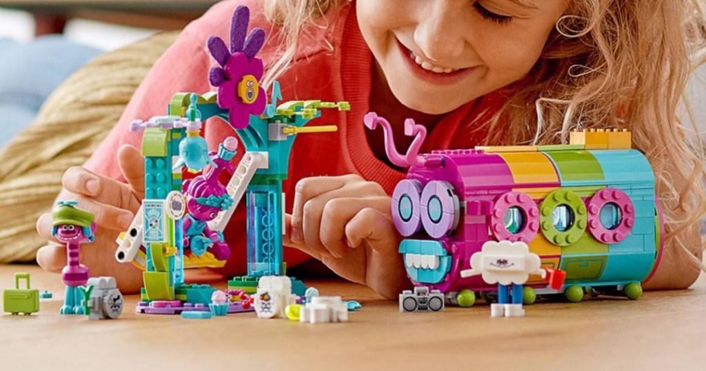 girl playing with trolls lego bus