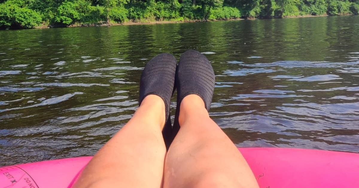 legs wearing black water shoes on pink innertube