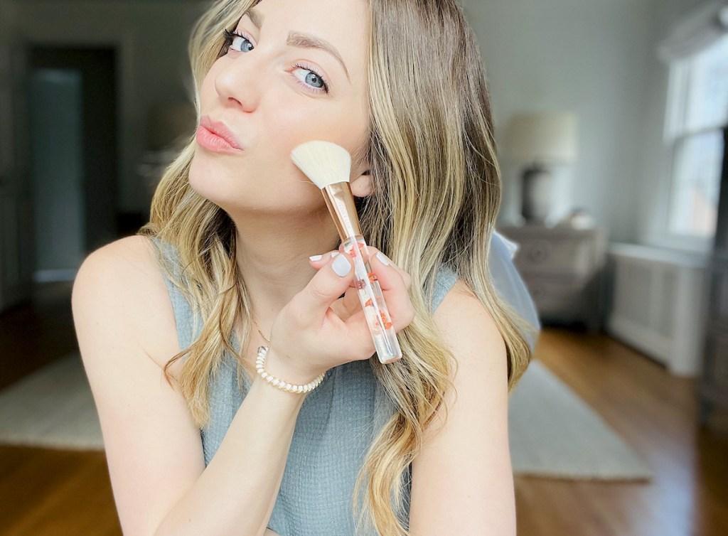 woman using floral makeup brush on cheek
