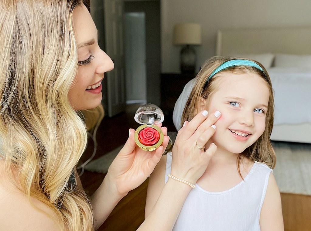 woman putting rose blush on girls face