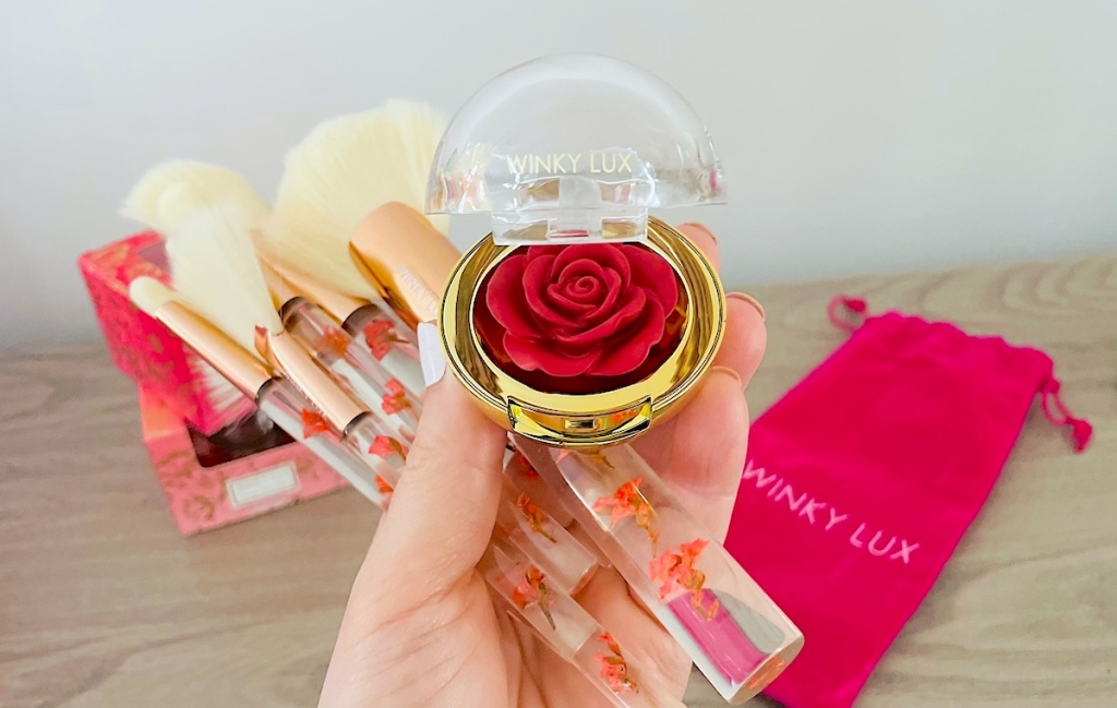 hand holding rose shaped makeup with brushes