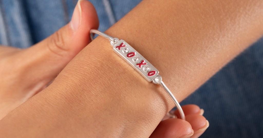 Woman wearing an XOXO themed charm bracelet