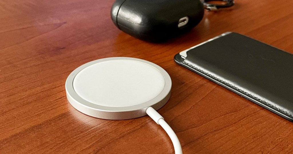 white apple wireless charger on a wood table