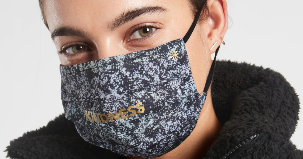 """woman wearing a printed mask that says """"kindness"""""""